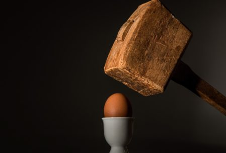 wooden mallet over brown egg