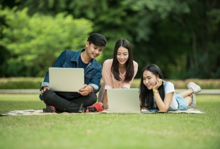 asian college students on grass with laptops